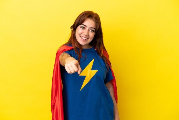 Superhelden-rothaarigefrau, die auf gelbem hintergrund isoliert ist, zeigt mit einem selbstbewussten ausdruck mit dem finger auf dich