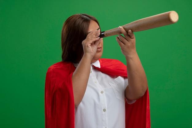 Superheldenfrau mittleren alters, die blickgeste mit baseballschläger lokalisiert auf grün zeigt
