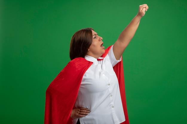 Superheldenfrau mittleren alters, die in der profilansicht steht, die faust auf grünem hintergrund anhebt