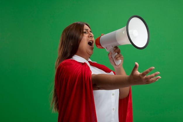 Superheldenfrau mittleren alters, die seite betrachtet, spricht auf lautsprecher, der hand an kamera lokalisiert auf grünem hintergrund heraushält