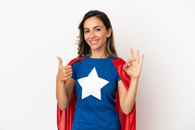 Superheldenfrau über isoliertem weißem hintergrund, die ein ok-zeichen und eine daumen-hoch-geste zeigt
