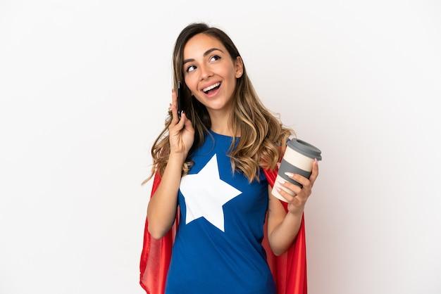 Superheldenfrau über isoliertem weißem hintergrund mit kaffee zum mitnehmen und einem handy