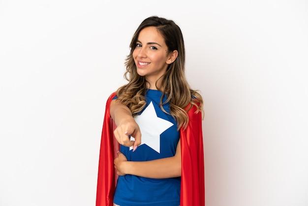 Superheldenfrau über isoliertem weißem hintergrund zeigt mit einem selbstbewussten ausdruck mit dem finger auf dich