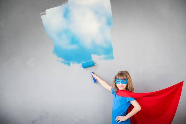 Superheldenkind, das blauen himmel an der wand malt. kind hat spaß zu hause. frühjahrssanierungskonzept