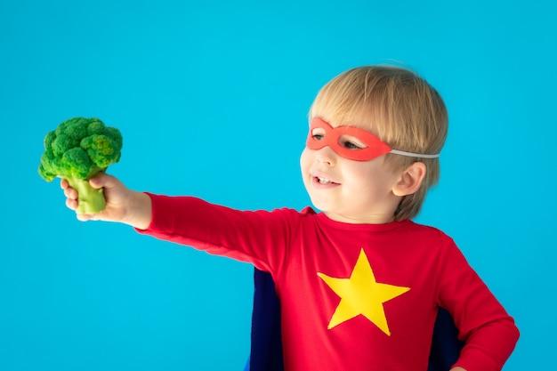Superheldenkind, das brokkoli hält