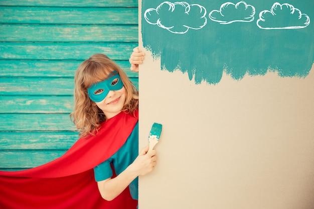 Superheldenkind, das die wand mit blauer farbe malt. kind hat spaß zu hause. frühjahrssanierungskonzept