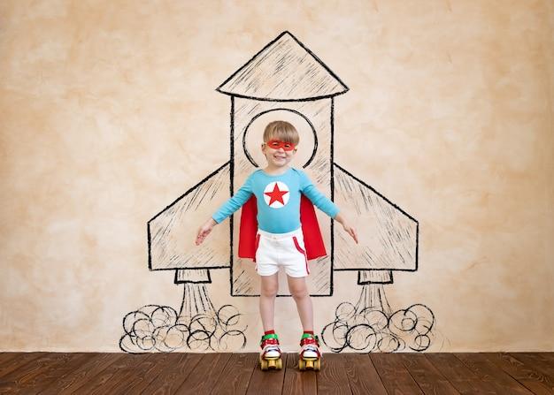 Superheldenkind, das spaß hat porträt des kindes zu hause. superheldenkind spielt. lustiger raketenjunge. kinderphantasie und traumkonzept