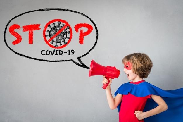 Superheldenkind, das über lautsprecher über covid-19 spricht.