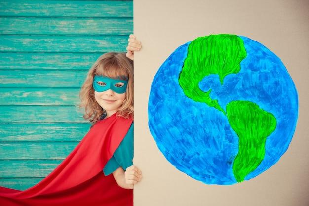 Superheldenkind, das zu hause spielt kind versteckt sich hinter karton-banner-rohling