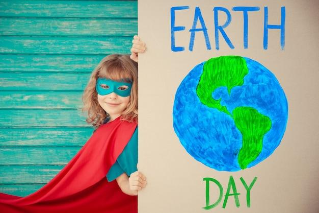 Superheldenkind, das zu hause spielt kind versteckt sich hinter pappe mit handgezeichnetem planeten. konzept zum tag der erde