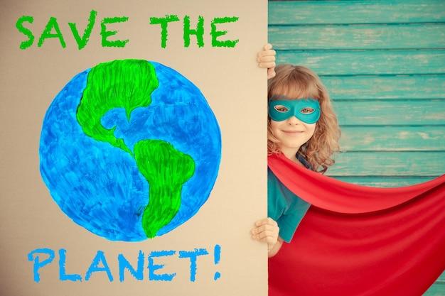 Superheldenkind, das zu hause spielt superheldenkind, das sich hinter pappbanner versteckt. handgezeichneter planet. konzept für den tag der erde