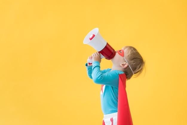 Superheldenkind gegen gelben papierhintergrund. superheldenkind mit roter maske und umhang. kindheitstraum und fantasiekonzept