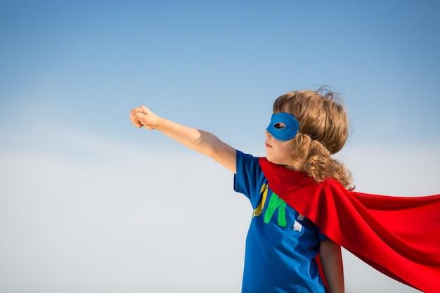 Superheldenkind gegen hintergrund des blauen himmels. frauenpower-konzept