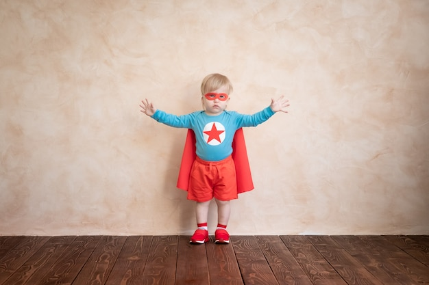 Superheldenkind. kind, das zu hause spielt. erfolgs- und gewinnerkonzept