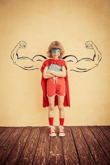 Superheldenkind mit gezeichneten muskeln gegen schmutzwandhintergrund erfolgs- und gewinnerkonzept