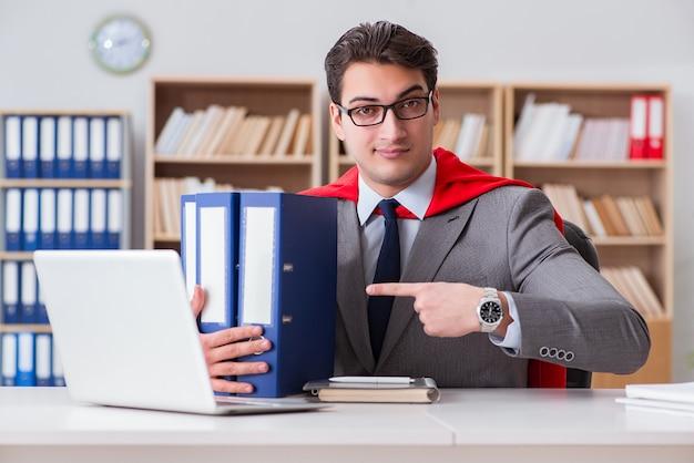 Superheldgeschäftsmann, der im büro arbeitet