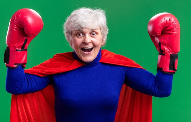 Superheldin der älteren frau, die roten umhang mit boxhandschuhen trägt, die glücklich und aufgeregt die hände heben, die über grünem hintergrund stehen