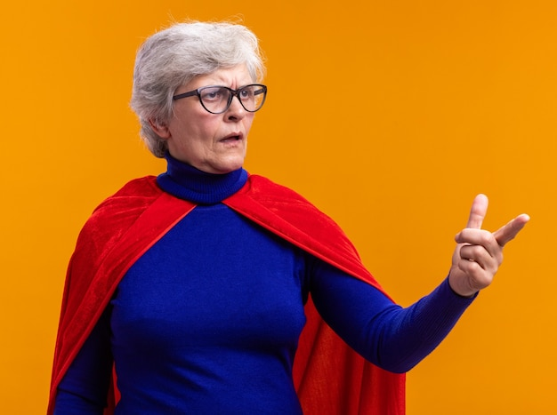 Superheldin der älteren frau mit brille mit rotem umhang, die mit verwirrendem ausdruck beiseite schaut