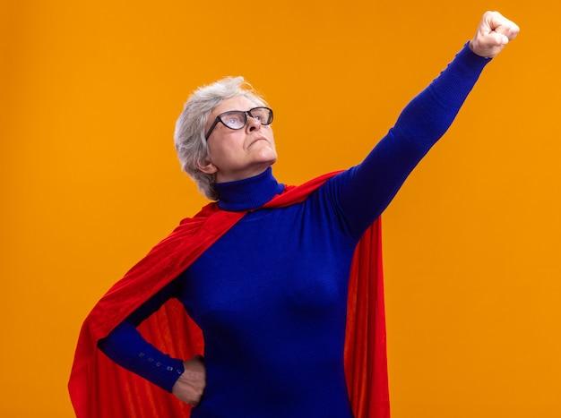 Superheldin der älteren frau mit brille mit rotem umhang, die nach oben schaut und gewinnergeste mit der hand macht, die bereit ist, zu helfen und zu kämpfen