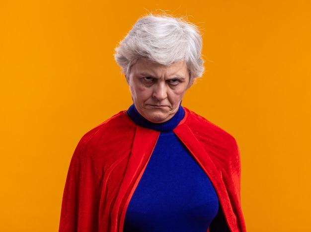 Superheldin der älteren frau mit rotem umhang, der die kamera mit wütendem gesicht stirnrunzelnd anschaut