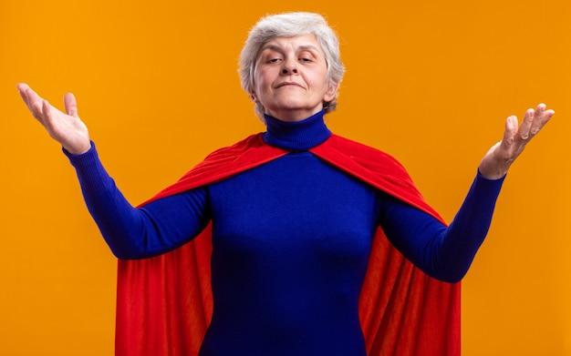 Superheldin der älteren frau mit rotem umhang, der mit selbstbewusstem ausdruck mit erhobenen armen über orange in die kamera schaut