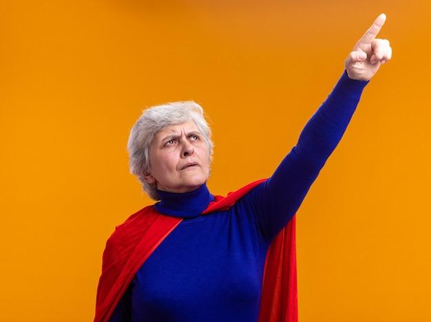 Superheldin der älteren frau mit rotem umhang, der mit stirnrunzelndem gesicht aufschaut, das mit dem zeigefinger nach oben über orange zeigt