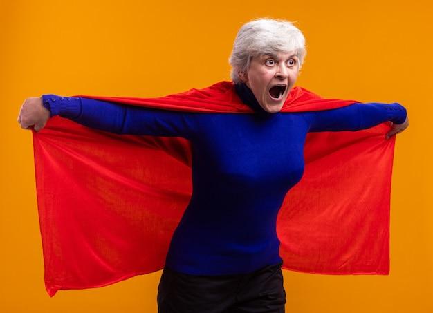 Superheldin der älteren frau mit rotem umhang, der überrascht beiseite schaut und schreit, während sie ihren umhang hält, der über orange fliegen wird