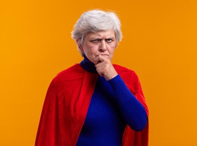 Superheldin der älteren frau mit rotem umhang, die verwirrt mit stirnrunzelndem gesicht auf orangefarbenem hintergrund aufschaut