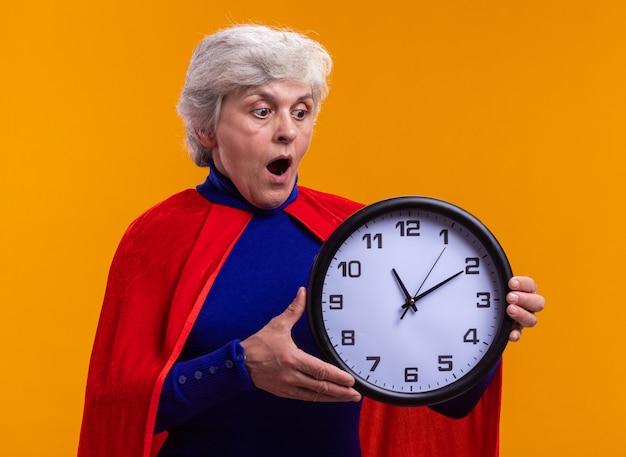 Superheldin der älteren frau mit rotem umhang mit uhr, die es erstaunt und überrascht betrachtet