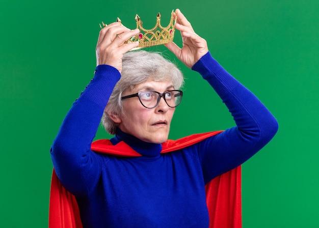 Superheldin der älteren frau mit rotem umhang und brille, die krone auf den kopf setzt und selbstbewusst auf grünem hintergrund aussieht