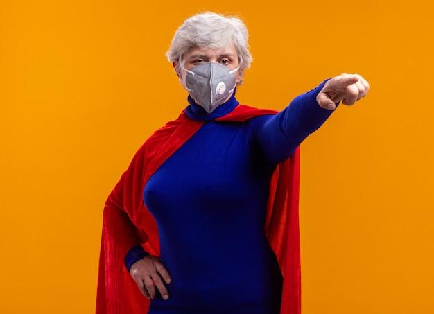 Superheldin der älteren frau mit rotem umhang und gesichtsschutzmaske, die auf etwas mit ernstem gesicht zeigt, das über orangefarbenem hintergrund steht