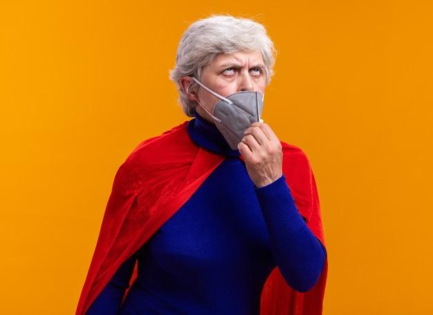 Superheldin der älteren frau mit rotem umhang und gesichtsschutzmaske rollt die augen müde und gelangweilt ab und setzt die maske auf orangefarbenem hintergrund ab