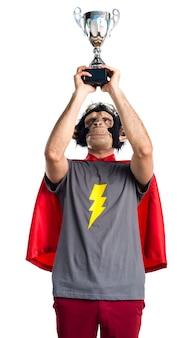Superhero affe mann hält eine trophäe