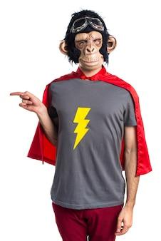 Superhero affe mann zeigt auf die laterale
