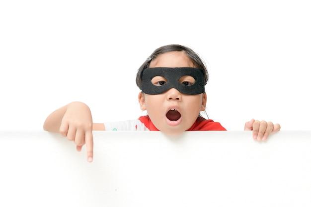 Superheromädchen, das auf weißes fahnenbrett zeigt