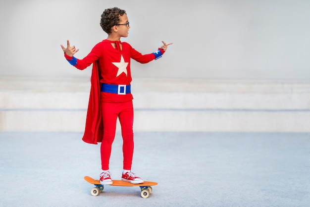 Supermann-kind, das fröhliches konzept des skateboards spielt