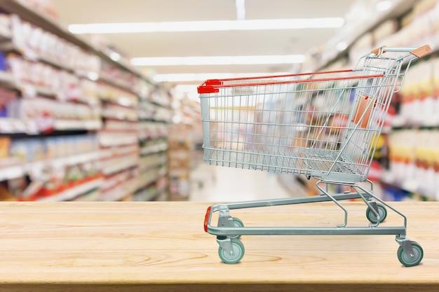 Supermarkt-einkaufswagen auf holztisch mit unscharfem hintergrund des ganges des lebensmittelgeschäfts