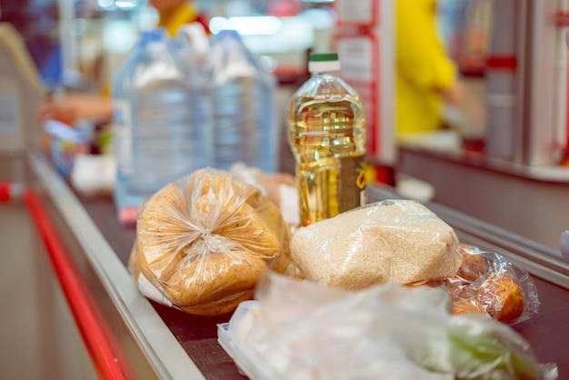 Supermarkt-kasse mit essen auf dem förderband zum einkaufen am wochenende