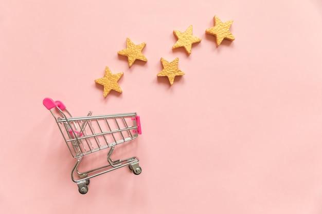Supermarkt lebensmittel push cart zum einkaufen und gold sterne bewertung isoliert auf rosa