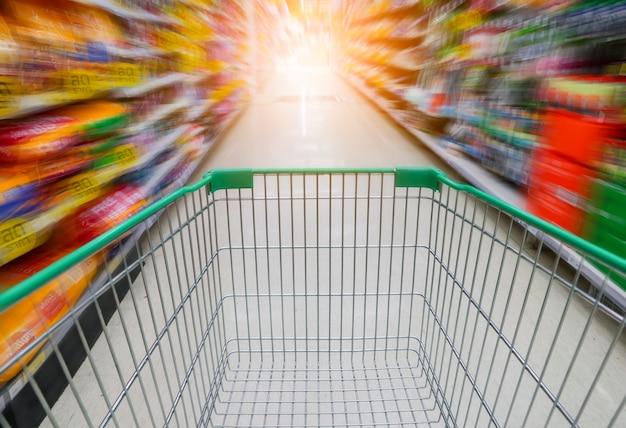 Supermarkt mit grünem einkaufswagen.