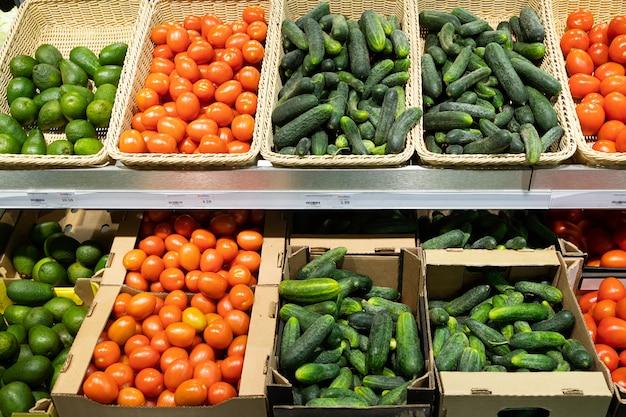 Supermarkt shopboard mit weidenkörben und kartons mit tomaten, gurken und avocado