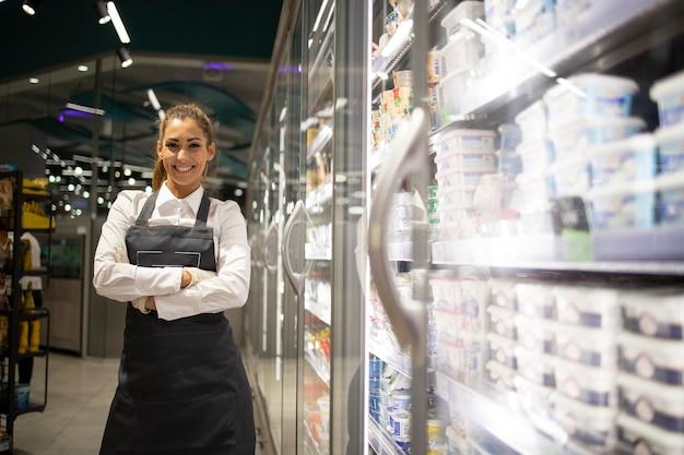 Supermarktarbeiter arrangiert gefrorenen fisch zum verkauf