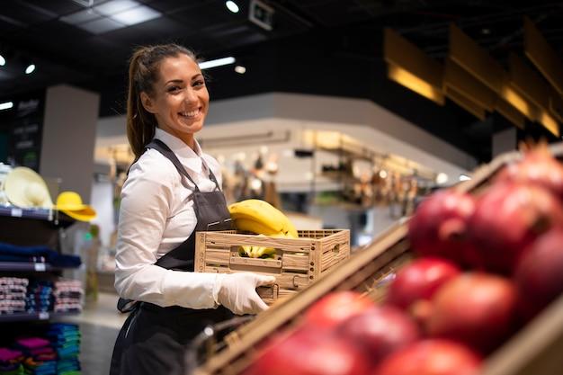 Supermarktarbeiter, der die obstabteilung mit lebensmitteln versorgt