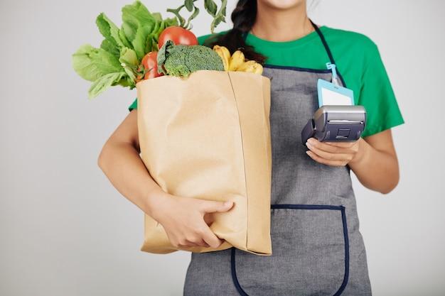 Supermarktarbeiter mit tüte mit lebensmitteln