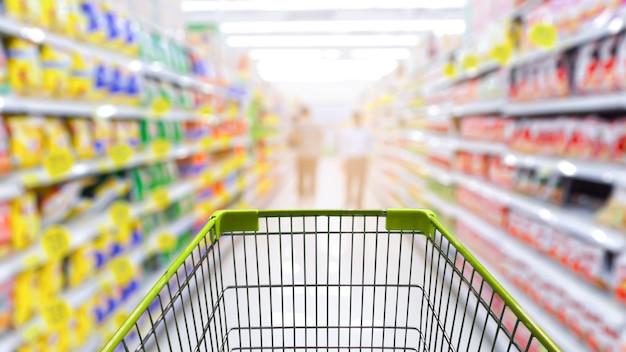 Supermarktgang mit leerem grünem einkaufswagen.