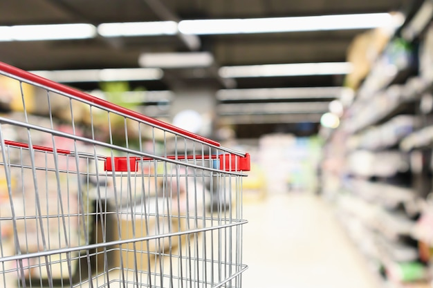 Supermarktgang verwischte hintergrund mit leerem roten einkaufswagen