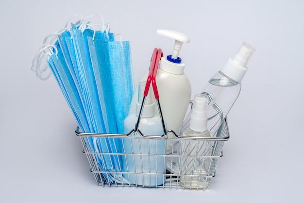 Supermarktkorb mit medizinischer schutzmaske und einer flasche alkohol-handgel-desinfektionsmittel. coronavirus-einkaufskonzept auf hellgrauem hintergrund