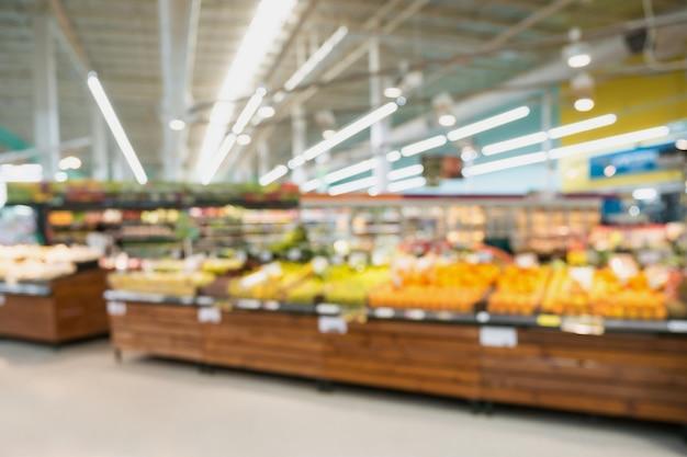 Supermarktlebensmittelgeschäft mit obst und gemüse auf regalen unscharfen hintergrund