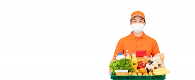 Supermarktlieferant, der medizinische maske trägt, während lebensmittel- und lebensmittelkorb isoliert hält