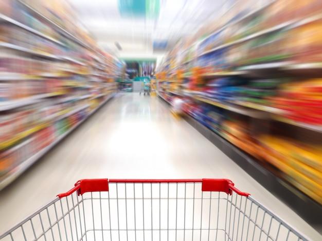 Supermarktregale gang verwischten hintergrund mit einkaufswagen in bewegung